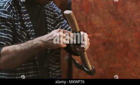 Man working in carpentry workshop. He wraps wooden handle of ax with leatherwork material. Men at work. Hand work. - Stock Photo