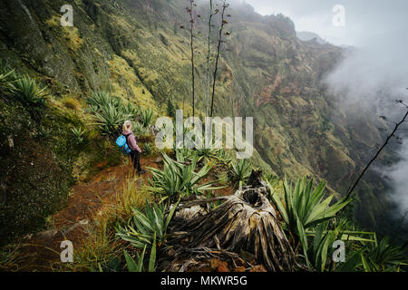 Female traveler staying on the cove volcano edge above the foggy green valley overgrown with agaves Santo Antao island in Cabo Verde - Stock Photo