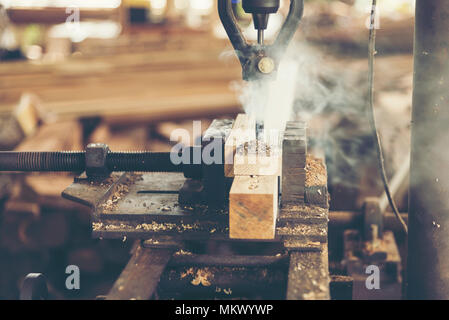 Close-up of carpenter cutting a wooden plank - Stock Photo