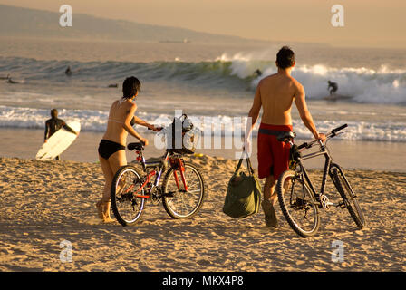 A young couple rides their bikes to  Venice Beach where surfers are riding waves in the late afternoon, Los Angeles, CA - Stock Photo