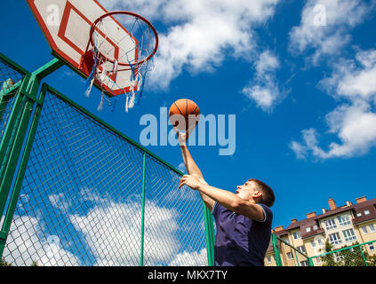 young man playing basketball in the courtyard on a sunny summer day - Stock Photo