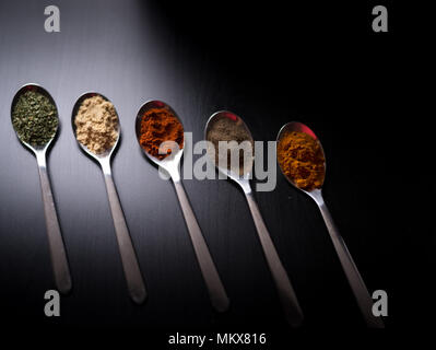 Spices colored in silver spoons, placed on a black wooden table. Pepper, pepper, salt, basil, mustard - Stock Photo
