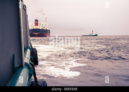 Anchor-handling Tug Supply AHTS vessel at work with FPSO tanker - Stock Photo