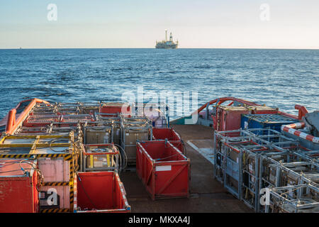 offshore supply boat delivers cargo to oil rig platform - Stock Photo