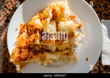 Balkan Bakery Breakfast Serving of Byrek me Gjizë (Burek Cheese PIe with Feta & Flaky Filo Pastry) in the Sun - Stock Photo
