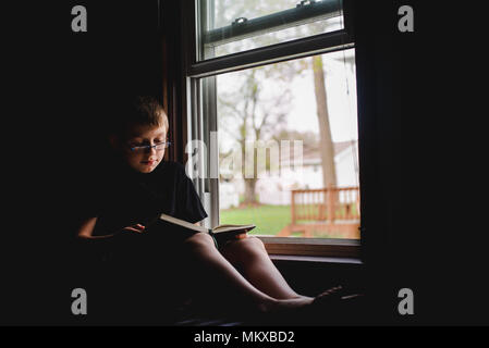 A 11-year old boy sits in an open window and reads a book. - Stock Photo