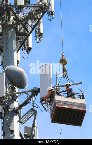 Two men suspended in the air via a cable while working on a cellphone tower in Ferndale, Washington, USA. - Stock Photo