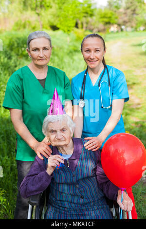 Senior disabled woman in a wheelchair celebrating birthday with friendly female caregivers outdoor - Stock Photo