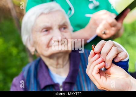 Elderly ill woman receiving pills from nurse outdoor, doctor writing medical prescription in the background - Stock Photo