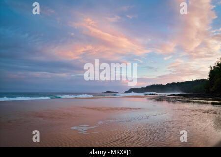 Beautiful sunrise over Secret Beach and a distant Kilauea Lighthouse along the North Shore on Hawaii's Island of Kauai. - Stock Photo