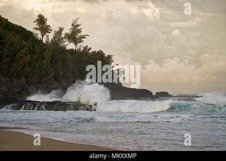 First light reveals crashing waves at Secret Beach along the North Shore on Hawaii's Island of Kauai. - Stock Photo