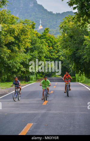 Lopburi, Thailand - July 21, 2013: Three boys with different color shirts riding bicycles on rural road in Lopburi, Thailand - Stock Photo