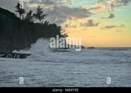 Sunset over Secret Beach as incoming waves pound the North Shore on Hawaii's Island of Kauai. - Stock Photo