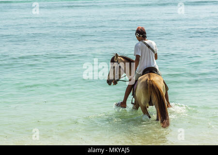 Indonesian man riding a horse in the blue and green shallow water close to the beach, april 24, 2018, Gili Trawangan, Indonesia - Stock Photo