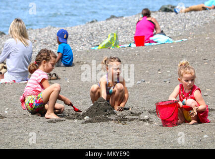 Children on the beach playing in the sand at Boulevard Park in Fairhaven, Bellingham, Washington, USA. - Stock Photo