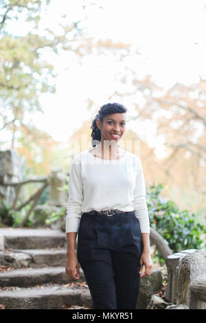 Cheerful black girl wearing white blouse standing near stone stairs in park. - Stock Photo
