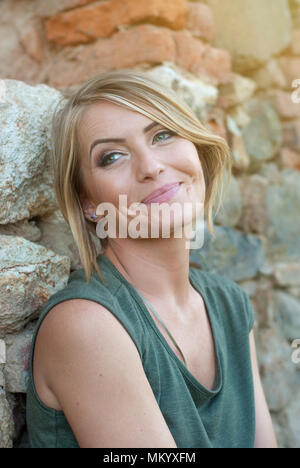 Beautiful happy blonde woman smiling and enjoying her time outside in park - Stock Photo