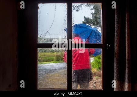 Ardara, County Donegal, Ireland  weather. 9th May 2016. A person struggles to work on a rainy, windy start to the day on Ireland's west coast. Seen through the window of a cottage. Credit: Richard Wayman/Alamy Live News - Stock Photo