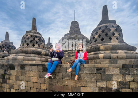 visitors enjoy the view over the Kedu Plain from the circular top terraces of 9th century Borobudur Buddhist temple, Central Java, Indonesia - Stock Photo