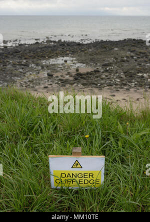 Danger cliff edge risk warning sign on on edge of wales coast path showing coastal erosion - Stock Photo