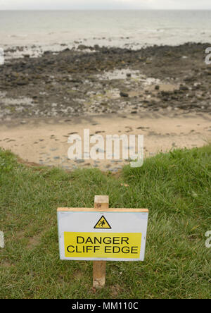 Danger cliff edge sign on on edge of wales coast path showing coastal erosion - Stock Photo