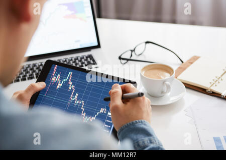 Touching stock market graph on a touch screen device. Trading on stock market concept. - Stock Photo