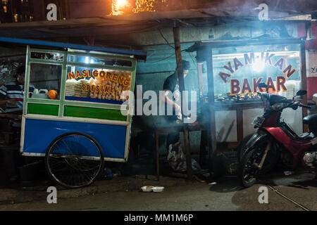Two street vendors selling fresh grilled fish and various snacks - Stock Photo