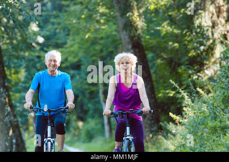 Happy and active senior couple riding bicycles outdoors in the park - Stock Photo
