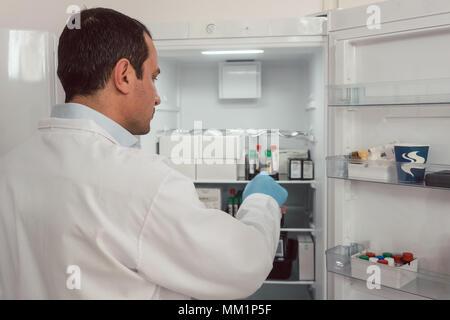 Lab technician storing blood samples in fridge - Stock Photo