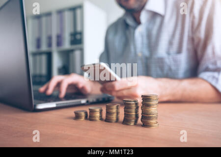 Coin stacker, businessman with stacked money in the office doing accountancy, budgeting and tax calculations - Stock Photo