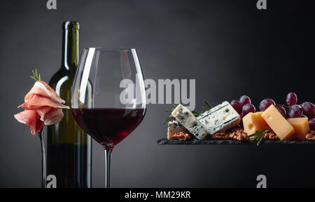Glass of red wine with various cheeses , fruits and prosciutto on a black background. Copy space . - Stock Photo