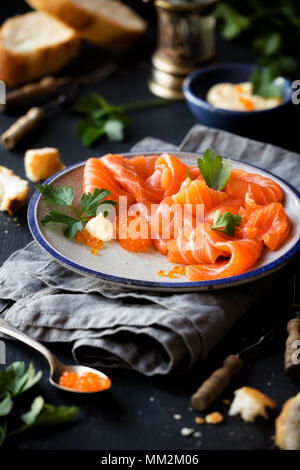 Smoked salmon slices with salted salmon caviar decorated with fresh parsley leaves - Stock Photo