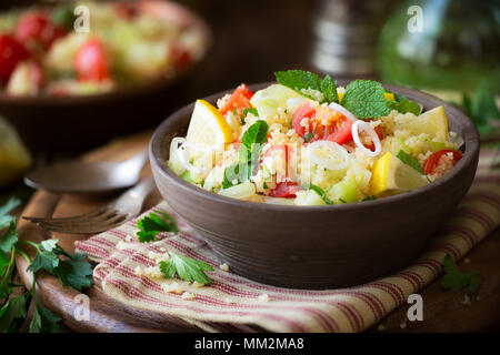 Vegetarian tabbouleh - delicious couscous salad with cherry tomatoes, cucumbers, fresh mint and parsley leaves. - Stock Photo