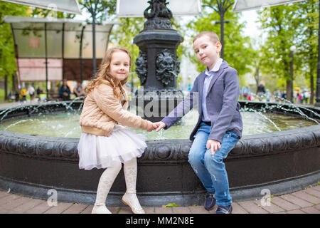 boy holding girl's hand. Children sitting at the fountain outdoor. Love friendship fun concept. Best friends forever. Small adults - Stock Photo