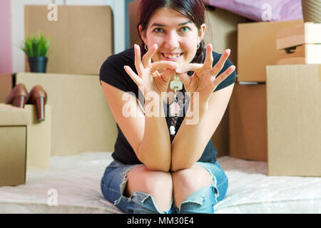 Photo of young brunette with keys from apartment in apartment - Stock Photo