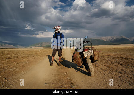 Motorcycle traveler man in helmet with suitcases standing on extreme rocky road in a mountain valley in cloudy weather on the background of endless st