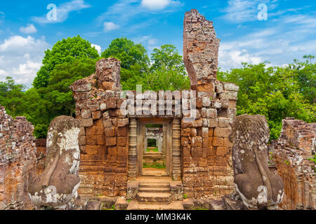 Close-up of the western laterite brick tower ruin, viewed from the top terrace behind the guardian lion statues of Cambodia's East Mebon temple. - Stock Photo