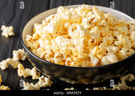 Popular snack: salted popcorn with cheddar cheese and parmesan in a bowl close-up on the table. horizontal - Stock Photo