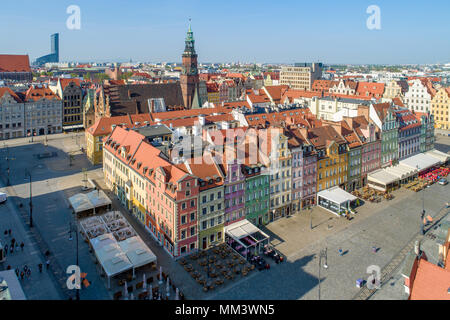 Poland, Wroclaw. Market Square (Rynek) with old historic tenements, gothic city hall and outdoor restaurants. Aerial view. Early morning. - Stock Photo