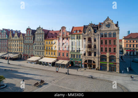 Poland, Wroclaw. Market Square (Rynek) with old historic tenements and outdoor restaurants. Aerial view. Early morning - Stock Photo