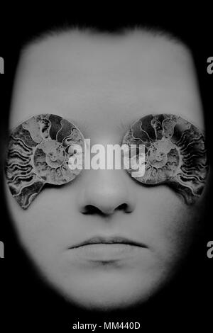 black and white image of a young Caucasian woman with ammonite fossils over eyes - Stock Photo