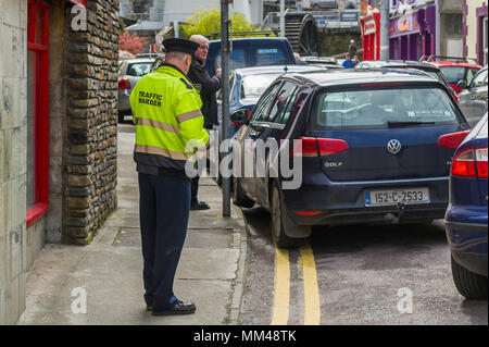 Irish Traffic Warden issues a parking ticket to a car which is parked on double yellow lines and the pavement in Bantry, County Cork, Ireland. - Stock Photo