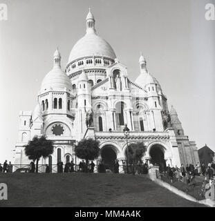 1950s, historical picture of the Basilica of the Sacred Heart of Paris, more commonly known simply as Sacre-Couer, a Roman Catholic Church built on top of the hill of Montmartre, Paris, France. This iconic monument was consecrated in 1919 and is the second most visited religious building in Paris. - Stock Photo