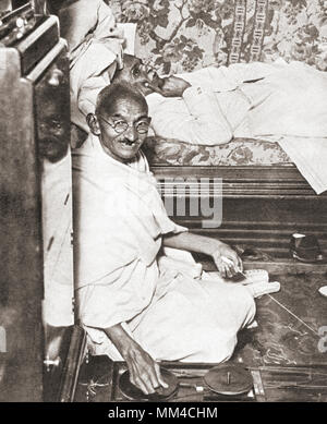 Mohandas Karamchand Gandhi, aka Mahatma Gandhi,1869 – 1948. Indian activist, leader of the Indian independence movement against British rule.  Seen here at the Round Table Conference, 1931. On the floor beside him is his spinning wheel, a symbol of his attempt to resurrect Indian industry at the expense of British trade.  From The Pageant of the Century, published 1934