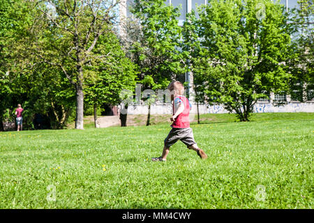 Prague, Czech Republic, 28 April 2018  little boy in trick and shorts running in park on grass in the background trees - Stock Photo