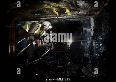 A miner drilling underground in South African gold mine. - Stock Photo