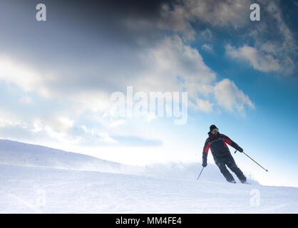 Skier on piste running downhill - Stock Photo