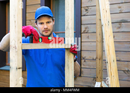 construction worker check the level of wooden frame - Stock Photo