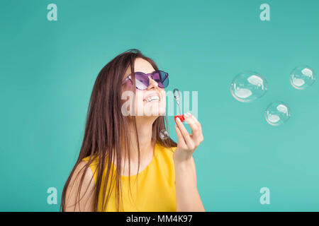Beautiful brunette girl wears sunglasses making soap bubbles on blue background - Stock Photo