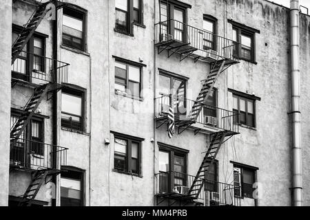 Black and white picture of old building with fire escapes, one of the New York City symbols, USA. - Stock Photo